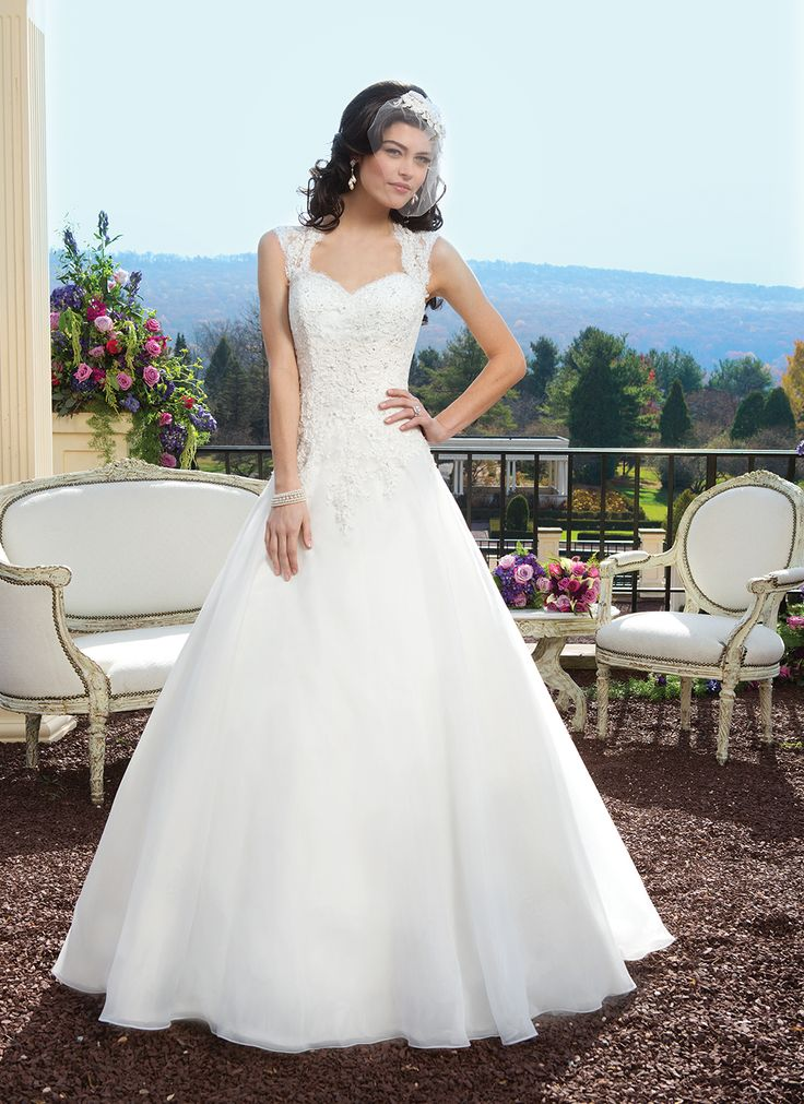 Sincerity wedding dress style 3809 Alencon beaded lace over organza ball gown featuring a Queen Anne  neckline. The gown is finished with a keyhole back, covered buttons over  the back zipper and a chapel length train.