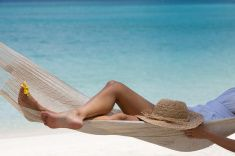 Woman relaxing in hammock on tropical beach stock photo