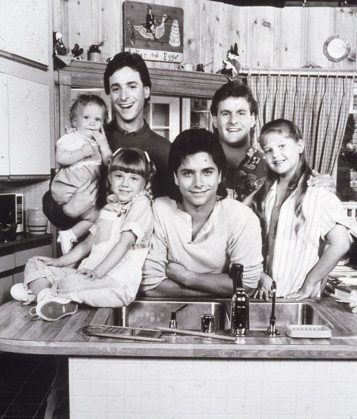 Full House - Promotional portrait of the cast L-R: Ashley or Mary Kate Olsen, Bob Saget, David Coulier, Candace Cameron, John Stamos, and Jodie Sweetin, circa 1987