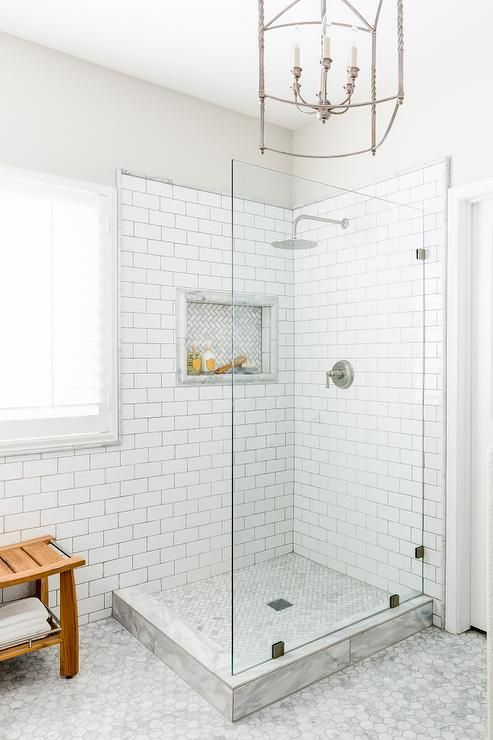 Chic master bathroom boasts walls painted Behr Silver Drop fitted with a corner walk-in shower clad in white subway tiles accented with dark grout fitted with a marble herringbone tiled shower niche over a matching herringbone shower floor illuminated by a Ballard Designs Carriage House Chandelier.