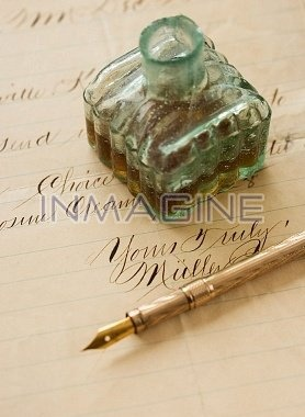 Quill pen and ink bottle on old letter photo