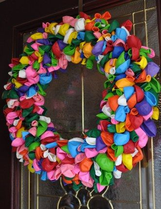 ballon wreath -  used 288.  Buy an 18-inch straw wreath, leave the plastic wrap on it and use greening pins (also called floral pins — they're sort of U-shaped and can be found in the artificial flower section at craft stores) and just pinned the balloons all over the wreath.
