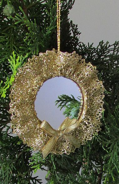 This Christmas tree decoration is a budgie mirror. I first removed the bell, then painted the plastic frame with gold model aircraft paint and glued a length of gathered gold lace around the frame on either side, finishing it off with a tiny gold bow.