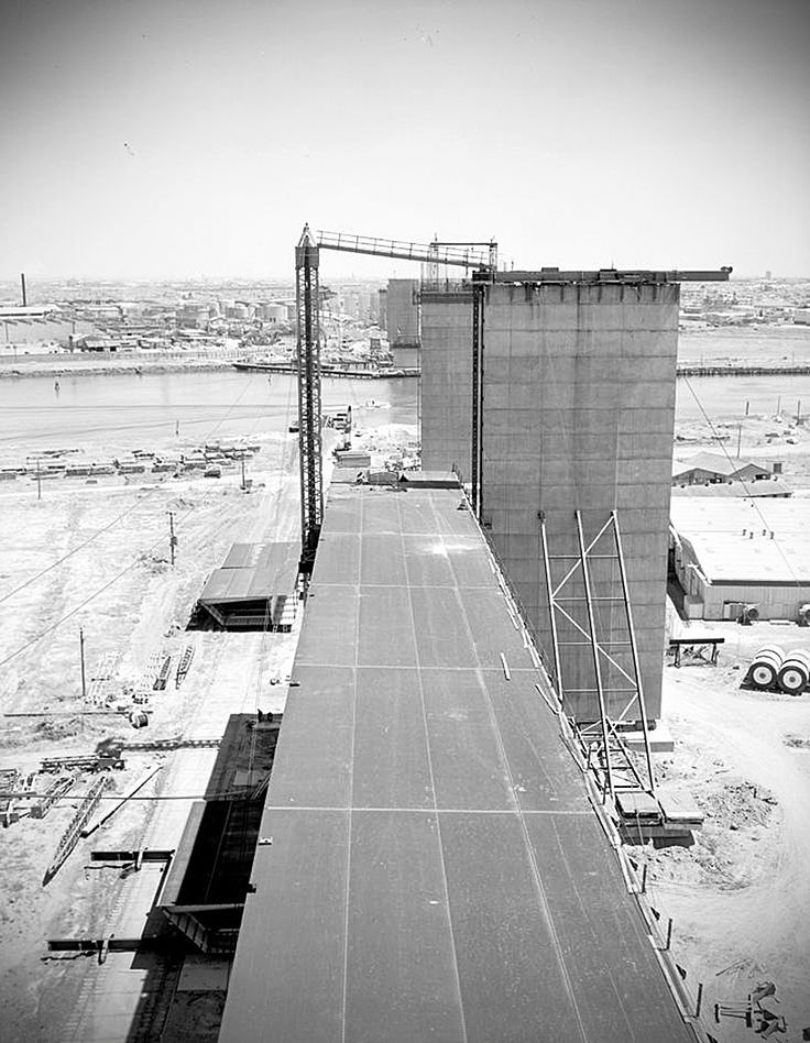 The construction of the West Gate Bridge on 12 November 1969, as seen from Douglas Parade and Hyde Street, Spotswood and looking towards Port Melbourne. The main bridge span is being raised to be positioned between its two piers.