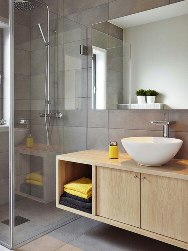 Wood cabinet, grey floor, bathroom. Wastafel met kastje