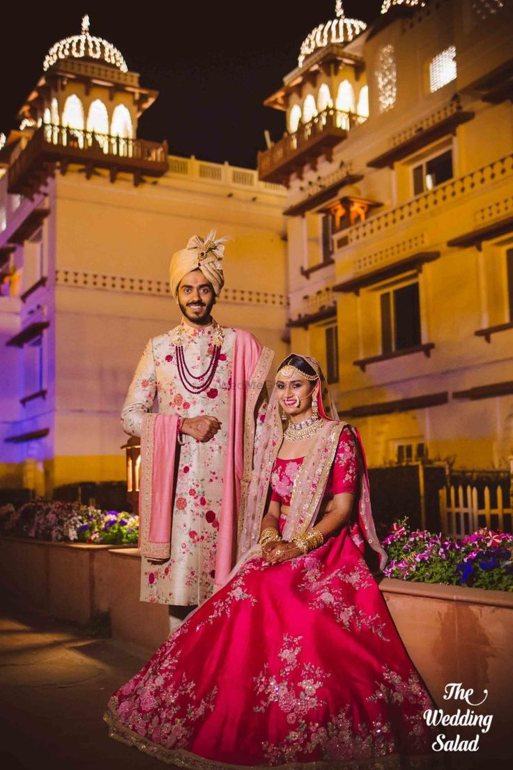 Co-ordinated bride and groom in a red-pink floral lehenga and ivory sherwani on wedding day| WedMeGood| #wedmegood #indianweddings #sabyasachi #redlehenga #ivory #ivorysherwani #bridaloutfits #sherwani #groomswear