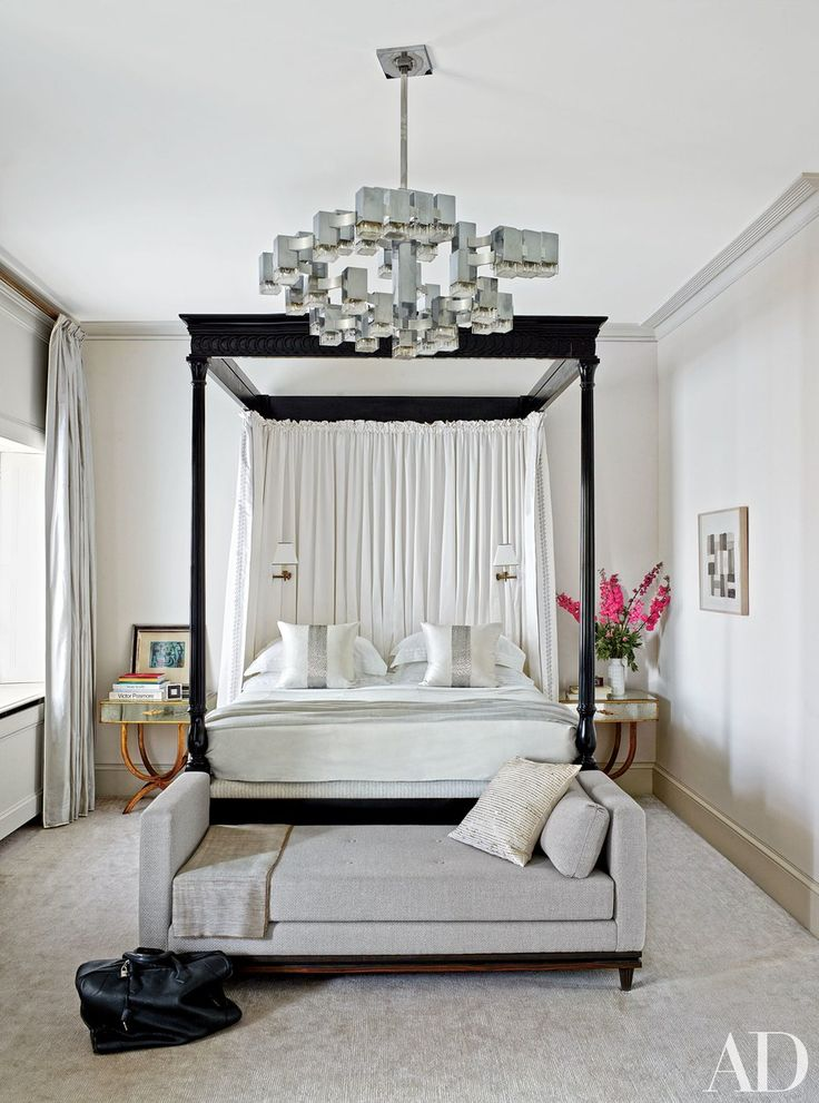 In the master bedroom of a Regent Park rowhouse by Veere Grenney, a 1970s Gaetano Sciolari light fixture from Galerie Yves Gastou joins an Veere Grenney Assoc. ebonized four-poster and a Francis Sultana daybed; the curtains are made of a Zimmer + Rohde silk, and the carpet is by Tai Ping.