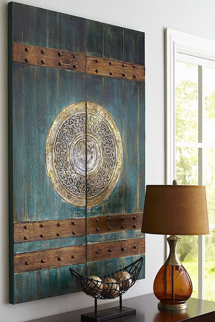 In ancient Chinese culture, lacquered red doors (called a vermillion gate) represented great wealth and luck. In modern living room culture, since the look proved popular with Pier 1 customers, we decided to add a teal theme to the painted wood and cotton canvas art—for good measure.: