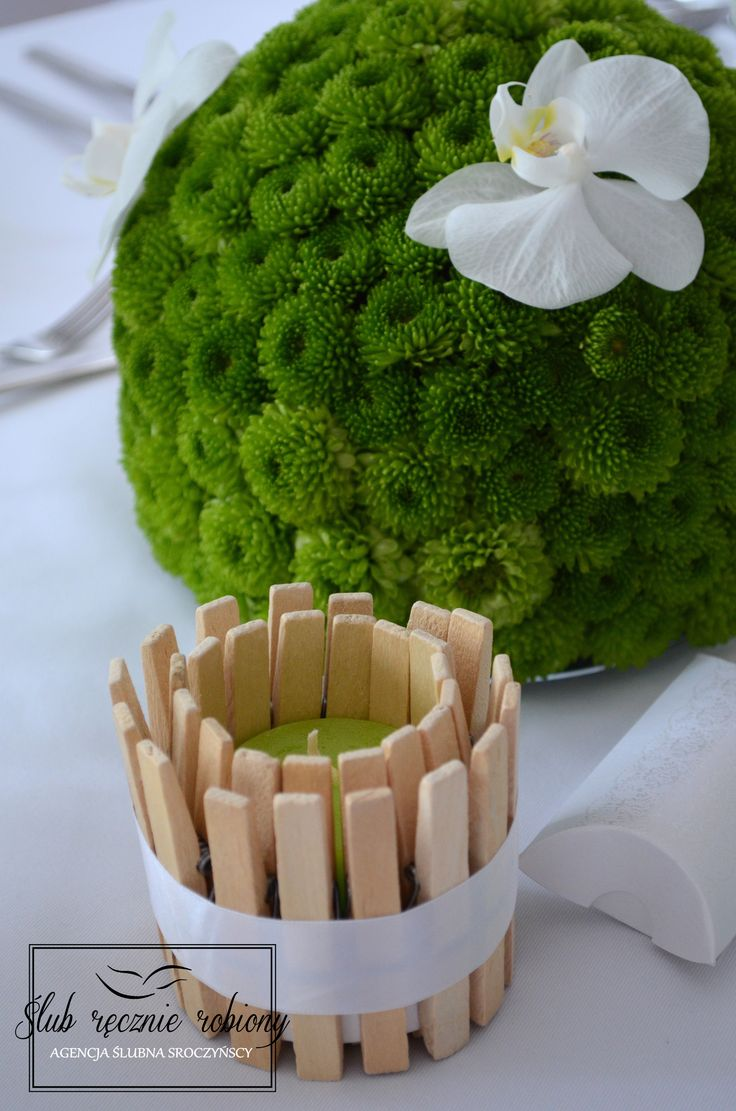 """Biało zielone dekoracje stołu weselnego w całości wykonane przez Agencję Ślubną Sroczyńskich """"Ślub Ręcznie Robiony"""". Świeże, wiosenne, z elementami stylu eko. Zielone świece w drewnianych świecznikach. Dekoracje kwiatowe, to kule z zielonych chryzantem, na których przysiadły niczym motylki białe storczyki. Upominki dla gości w białych pudełeczkach."""