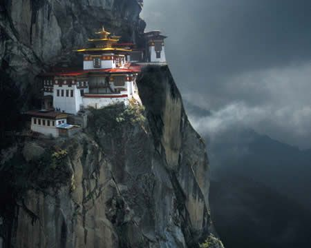 TAKTSHANG (Tiger's Nest) MONASTERY, Kingdom of Bhutan.  Built in 1692, this monastery hangs on a cliff at 10,200 feet-- 2,300 feet above the bottom of Paro valley.  The monastery includes seven temples which can all be visited, although it is only accessible on foot or by mule.