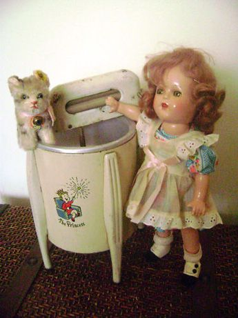1940s composition doll (unmarked but looks like an Arranbee doll) with a toy washing machine and a little Steiff cat. From Antique Toy Chest.
