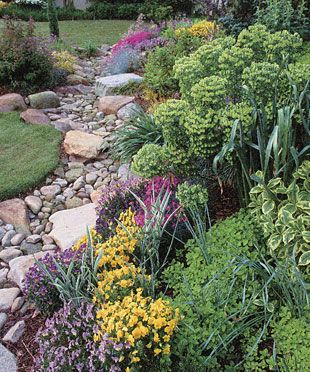 Instead of a poured concrete swale, these homeowners opted for a dry streambed lined with water-worn stones and edged with eye-catching plantings.