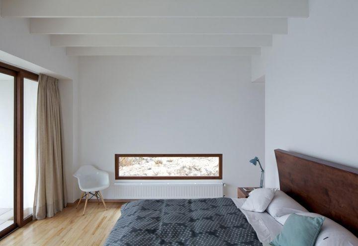 """La camera da letto padronale, sobria e accogliente, è aperta lateralmente da una sezione vetrata rettangolare, """"una reinterpretazione dell'oblò della nave"""""""