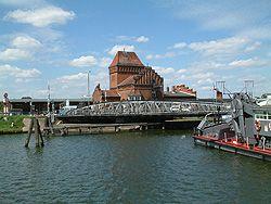 Drehbrücke-In Lübeck steht eine technische Spezialität, die Hub-Drehbrücke, die die Innenstadt mit dem Stadtteil St. Lorenz verbindet. Innerhalb von drei Minuten kann das 350 Tonnen schwere Bauwerk bei Bedarf angehoben und um 56 Grad gedreht werden. Eine Hydraulik sorgt für die Kraftübertragung, als Druckmittel dient normales Leitungswasser.