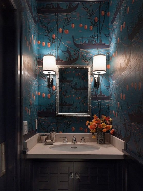 Stunning Chinoiserie style powder room with blue and orange Chinoiserie wallpaper over a black sink vanity with fretwork cabinet doors accented with crystal hardware and cream countertops which frame an oval shaped sink below a silver bamboo vanity mirror illuminated by polished nickel wall sconces on either side.