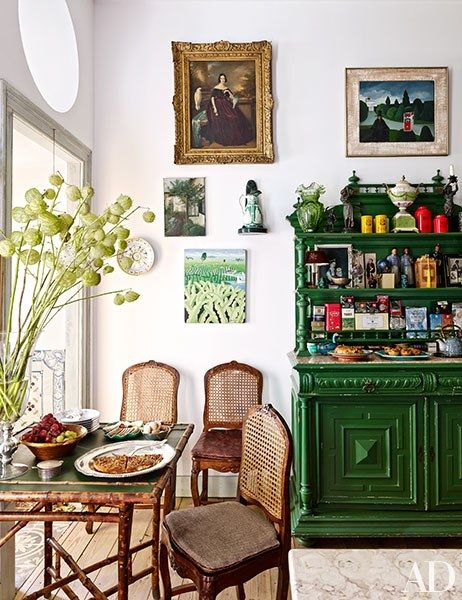 Antique Portuguese chairs are grouped with a bamboo table and a 19th-century sideboard in the kitchen's breakfast area | archdigest.com