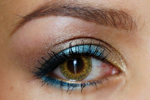 Teal op het ooglid, goudbruin in de arcadeboog en goud in de binnenste ooghoek. Afgemaakt met een goud oogpotlood op de onderste waterlijn en een teal potlood onder het oog, vervaagd met oogschaduw. Tot slot zwart oogpotlood langs de wimperrand.