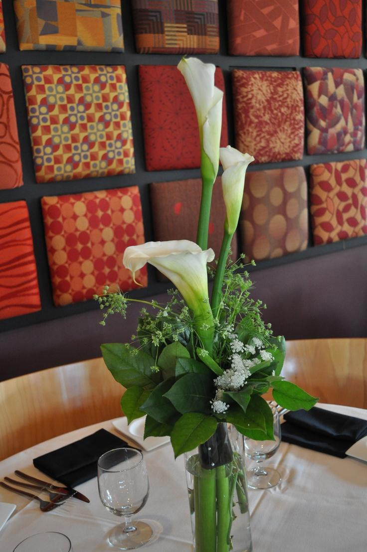 Tall calla lily arrangement in cylinder vase at bin