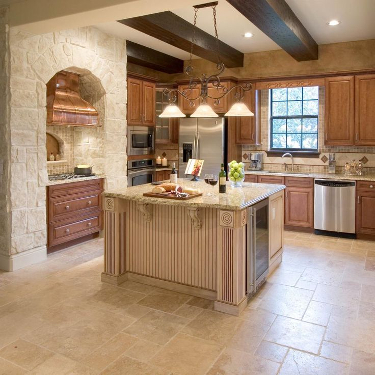 A seamless marriage of architecture and millwork is revealed in this Mediterranean kitchen. The stone arch highlights the copper hood, wooden beams and warm cabinetry, which blend with granite countertops throughout.