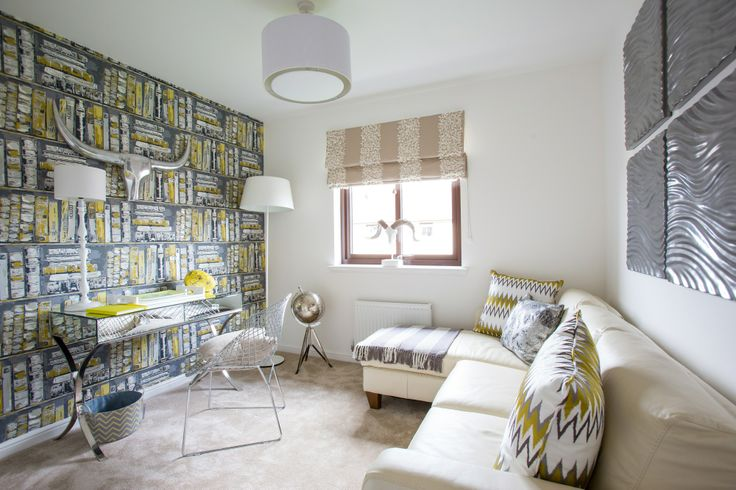 The study featuring grey and citrus yellow faux bookcase wallpaper