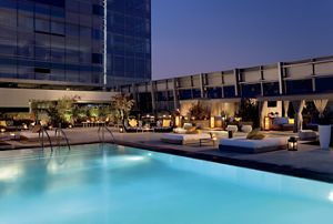 "Rooftop swimming pool and plush lounges on the 26th floor of the hotel.A communal table, small tables for two and a long bar with stools and a chalkboard column that reads ""cocktails""