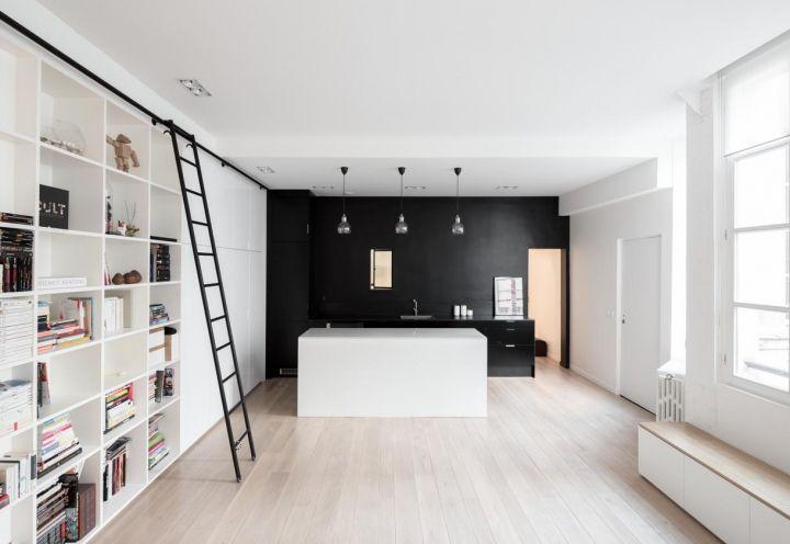 Il soggiorno ospita una capiente parete attrezzata a libreria, con scala a pioli che corre lungo un binario, per trovare con facilità il volume giusto. Sullo sfondo la cucina, con solidi mobili realizzati su misura