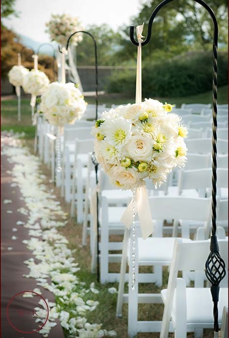Pomander balls created with white flowers and strands of crystal.