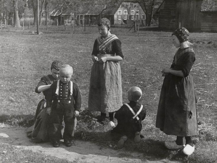 Groepje in Staphorster streekdracht, allen woonachtig in de omgeving van het 'armhuis' te Staphorst, gelegen in wijk G. De zittende vrouw is Trijntje Kooiker-Tuin, die de laatste hand legt aan de kleding van Jan Bloemhof. Het andere jongetje is Jan Kooiker. De meisjes zijn waarschijnlijk buurkinderen. De beide jongens zijn gekleed in hun opknapdracht. De vrouw en de meisjes zijn gekleed in daagse dracht. 1944 #Overijssel #Staphorst