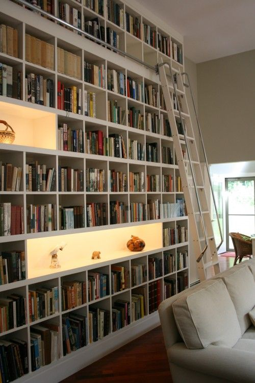 Floor-to-ceiling bookshelves with ladder and lighted showcases built in create a striking & functional wall.