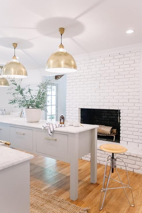 White and grey kitchen features a white brick fireplace facing a grey freestanding island with deep drawers adorned with brass pulls topped with white marble illuminated by a pair of Eugene Pendants atop a light wood floor.
