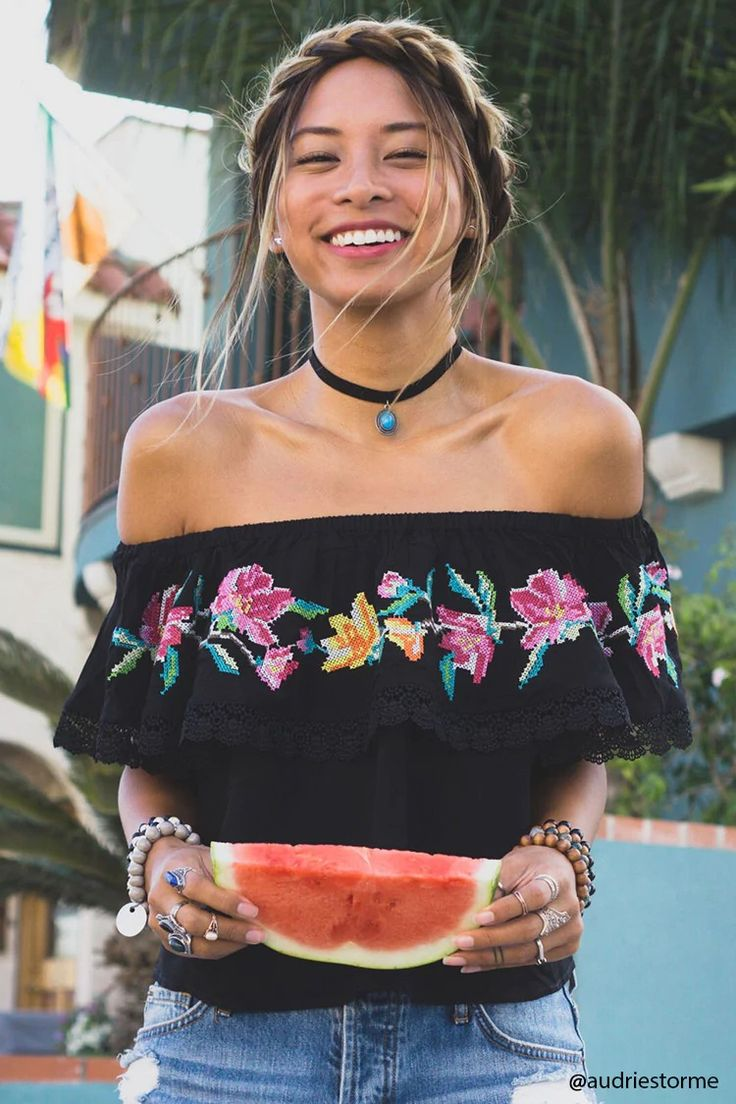 A woven top featuring an elasticized off-the-shoulder neckline, a flounce layer with crochet trim that falls into short sleeves, front floral embroidery on the flounce, and a flowy silhouette.