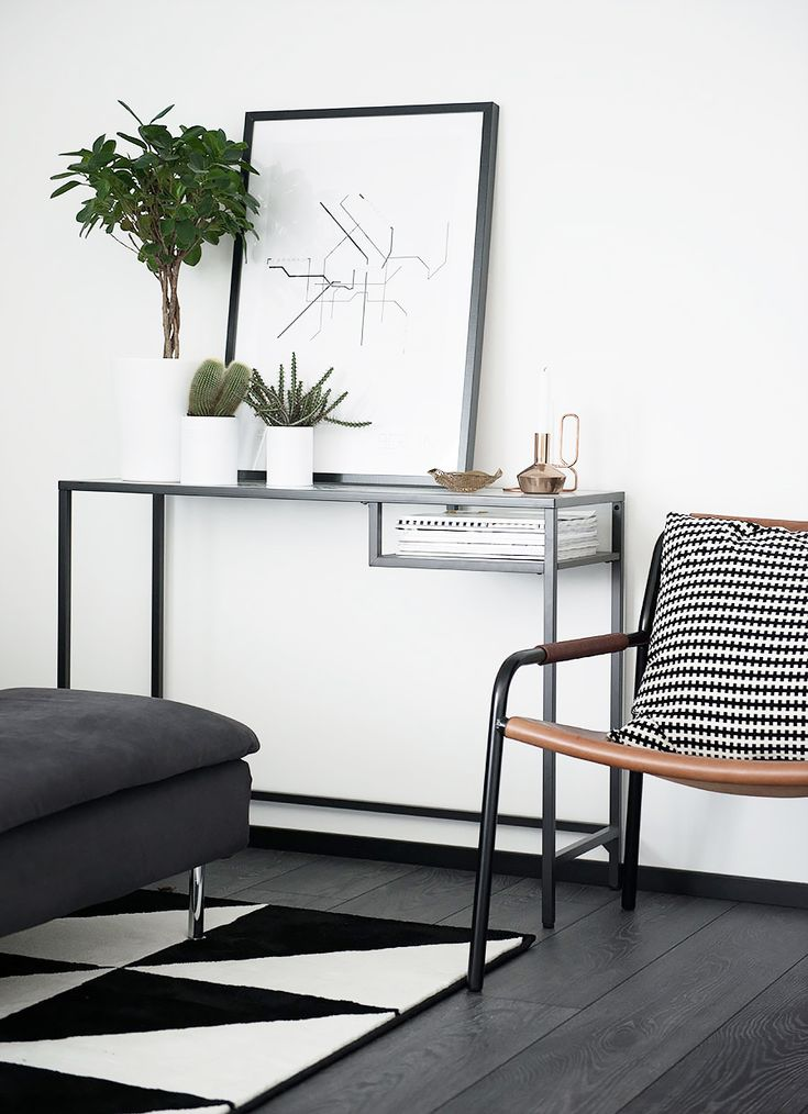 Black-and-white console table with leaning art and green indoor plants