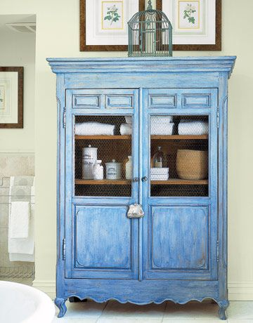 Pretty blue armoire in bathroom. An absence of built-in cabinetry carries the theme of Old World charm into the bathroom. For storage, an armoire fronted with chicken wire lets contents breathe — a big plus in a humid room. A small sterling-silver Edwardian purse dangles from the door handle.