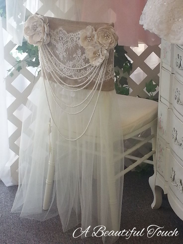 """This vintage inspired chair cover is a very popular rental for Brides that are hosting their reception at a vineyard, barn or other """"outdoorsy"""" venue. It evokes a feeling of country romance but yet has a dramatic flair with the long multi-strand pearls. It is a striking and unique rental. The Groom's chair cover is the matching burlap and alencon lace. Handmade with love by A Beautiful Touch."""