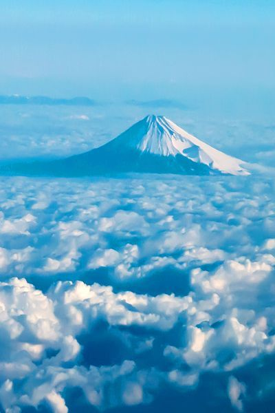 The majestic Mount Fuji in Japan, peeking through clouds.
