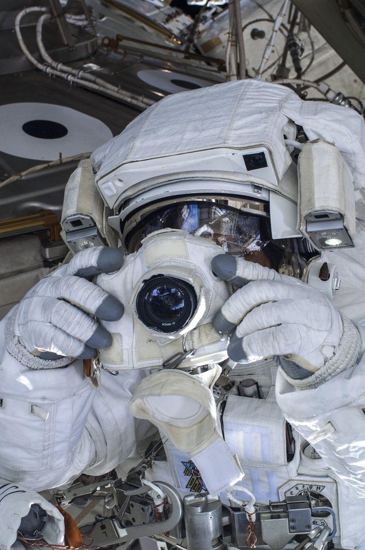 ESA astronaut Luca Parmitano uses a digital still camera during a spacewalk.