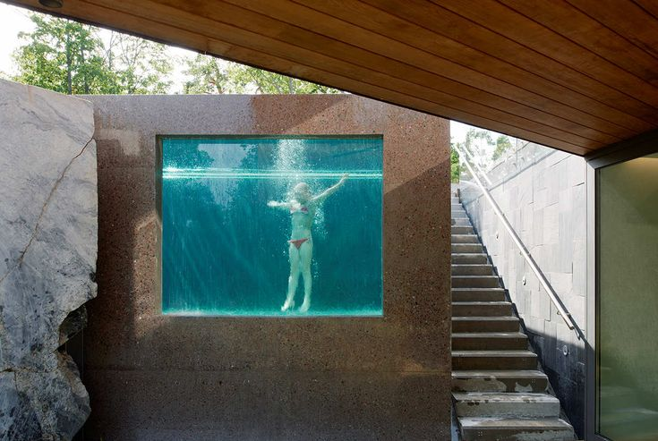 Villa Midgård by DAPstockholm - For a rather sober, secluded house in the Swedish forest, a blindingly blue swimming pool would have felt out of place. Therefore, the architects at DAPstockholm used dark concrete to create an atmosphere that is more woodland lake than residential infinity pool. But the best part is the unexpected glass panel that provides underwater views from the garden below.