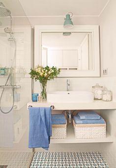 Baño pequeño con suelo hidráulico, mampara de cirstal, estante bajo el lavamanos con cestas y toallas en azul y blanco_413066
