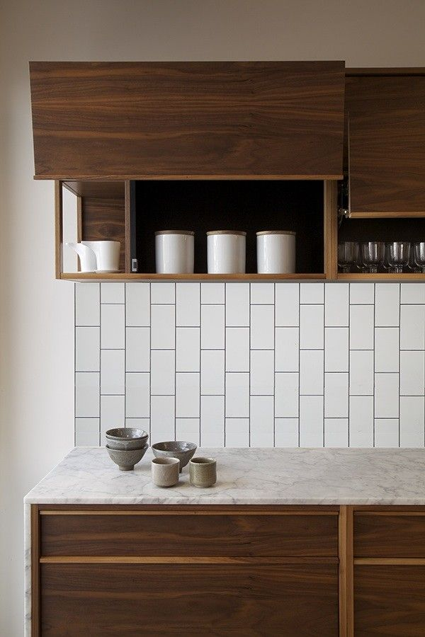 White vertical subway tile and wood cabinets in the kitchen
