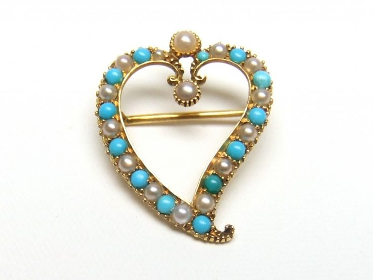 Witch's Heart Brooch. Victorian/Edwardian 15ct turquoise and pearl witch's heart. Circa 1900-10. The tail of a witch's heart twists to one side and is a shape that has been in use since the 15th century. It gained popularity in Scotland in the 17th century when it became known as a Luckenbooth, named for the closed booths in Edinburgh where they were sold as tokens to ward off evil spirits and protect loved ones. Tiny witch's hearts were often pinned to a baby's blanket as protection.