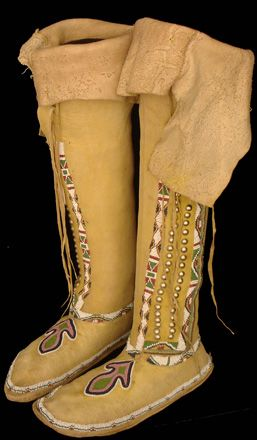 """Kiowa Adolescent's High-top Moccasins, 1880 The moccasins are constructed from suppled ochre dyed hide. Beadwork decorates the vamps, the sole seams and the warp-around cuffs. The beadwork consists of yellow, green and red geometric designs contained within a white lane. On the vamp, there exists a floral motif. The cuffs are further accented with green ochre; 18 3/4"""" tall."""