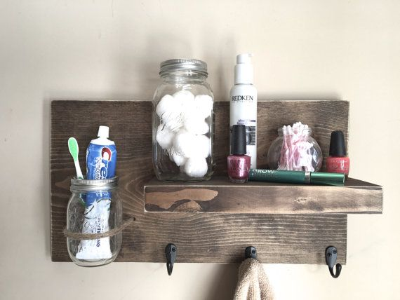 This rustic bathroom shelf is great for storage and hanging towels. The mason jar wall vase is great for works great as a toothbrush holder. It is made from reclaimed wood (pine) that has been stained dark walnut. This piece will also look great in a bathroom, entryway, mudroom or in any room in your house! It has 3 hooks great for hanging keys, hats, coats sweatshirts or towels. It measures 19.5w x 11 h x 5.25 d.