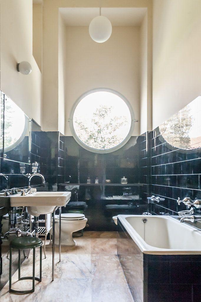 Nostalgisches Badezimmer mit blauen Fliesen und Bullaugen-Fenster