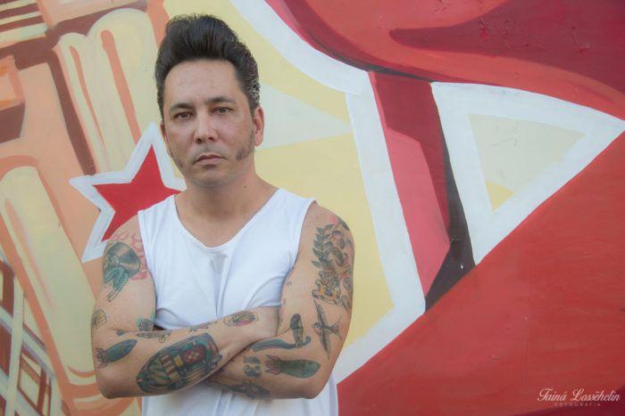 DJ Leandro com seu estilo rockabilly, topete e tatuagens old school.