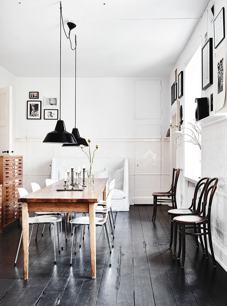 dining room with white walls, black floors, warm wood table, bentwood chairs, and industrial pendant lights