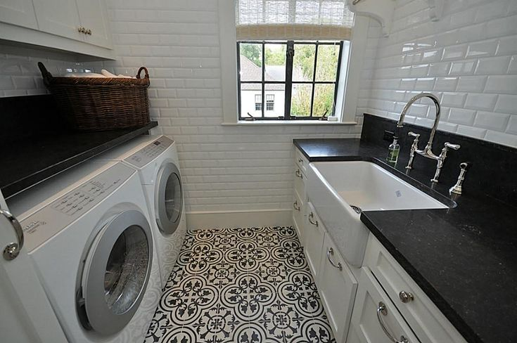 Beautiful laundry room with a concrete/cement tile floor, farm sink, and beveled subway tile walls.