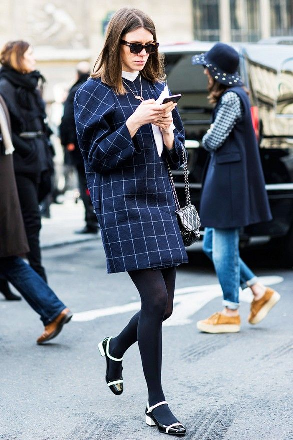 A plaid coat is worn with tights and black and white Mary Jane shoes