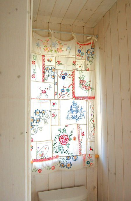 A bathroom window curtain made with a patchwork of vintage embroidered linens by Rosehip