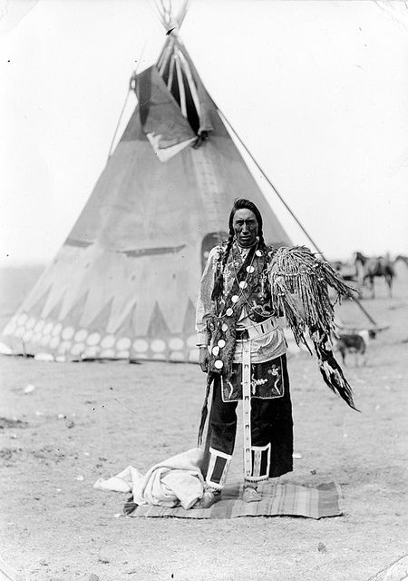 A medicine man standing in front of a teepee