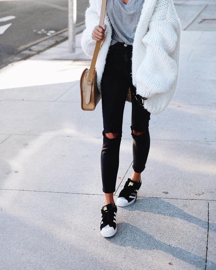 Gebreide cardigan en zwarte 7/8e ripped skinny jeans.